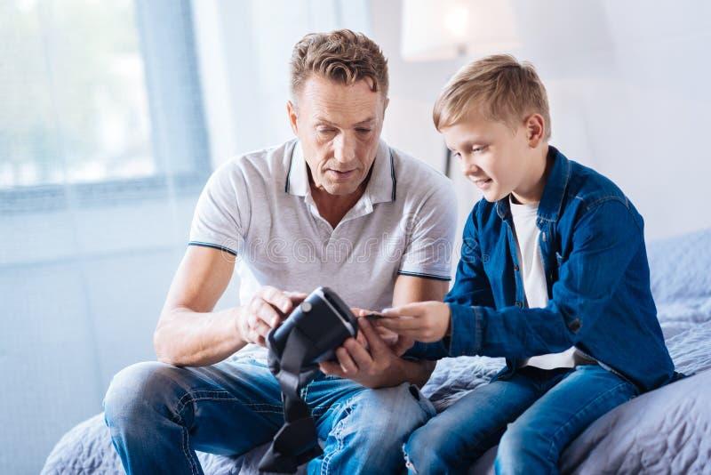 Будьте отцом и его пре-предназначенный для подростков сын рассматривая новый шлемофон VR стоковая фотография