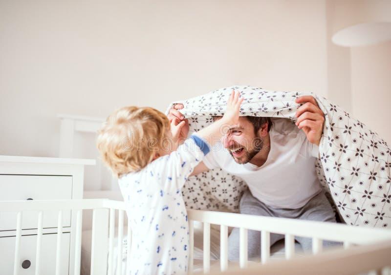 Будьте отцом при мальчик малыша имея потеху в спальне дома на времени ложиться спать стоковое изображение