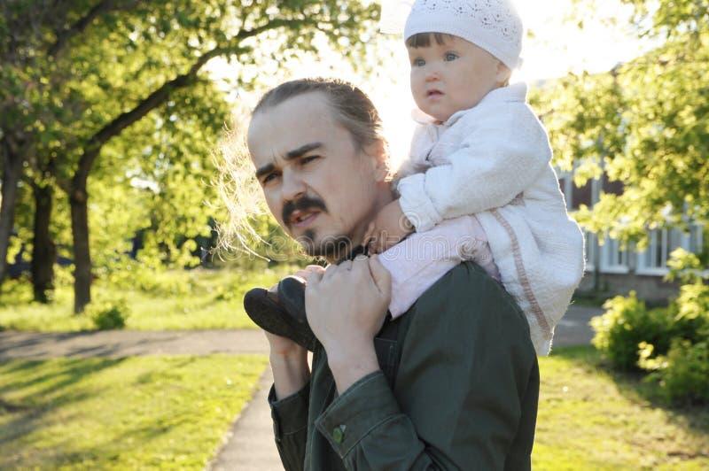 Будьте отцом при младенец дочери на плечах идя в парк на солнечном дне Портрет семьи подлинный стоковая фотография