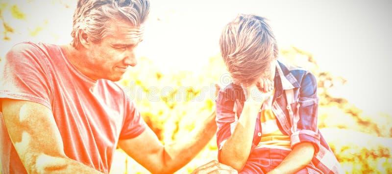Будьте отцом утешать его сына на пикнике в парке стоковое изображение rf