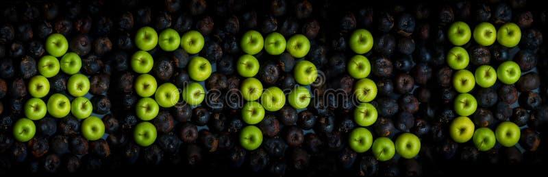 буквы алфавита выровнянные с зелеными яблоками стоковое фото rf