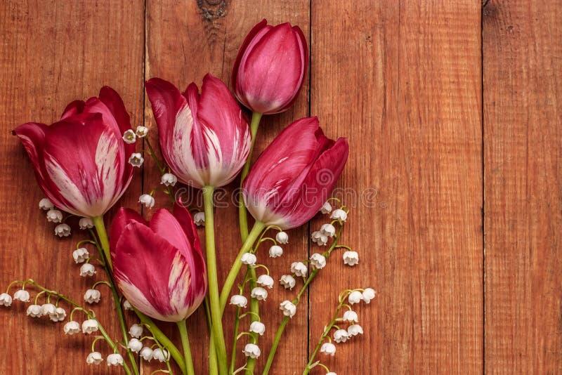 Букет ландыша и красных тюльпанов на коричневой деревянной предпосылке стоковое изображение rf