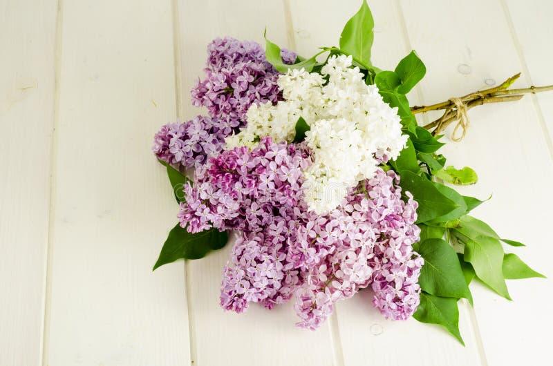 Букет белых и пурпурных ветвей сирени на деревянном столе стоковое фото