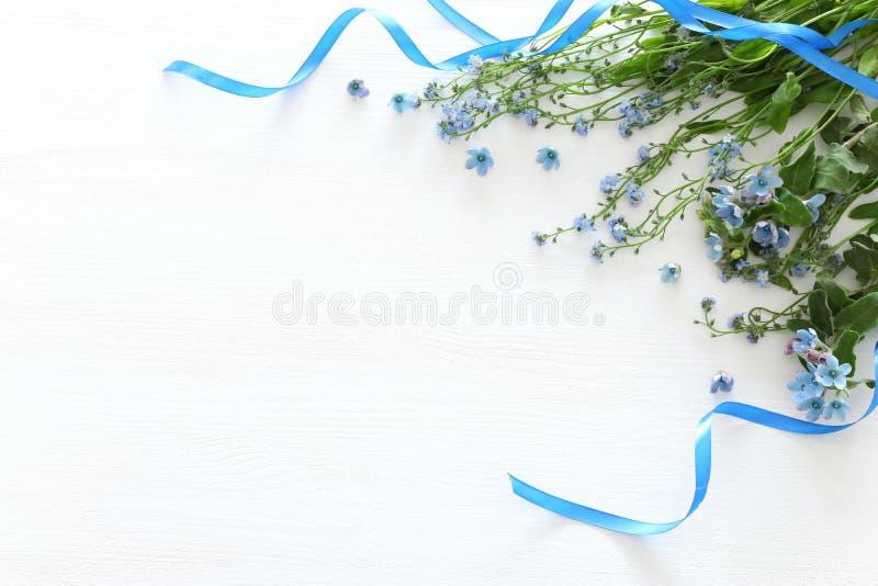 Букет весны голубых и чувствительных голубых цветков над белой деревянной предпосылкой Взгляд сверху, плоское положение стоковая фотография rf