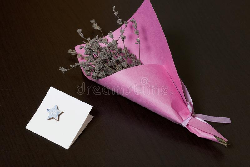 Букет высушенных цветков, в оболочке в покрашенной бумаге Около небольшой поздравительной открытки На темной предпосылке стоковые фотографии rf