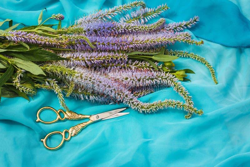 Букет диких лилаковых цветов и ножниц на синей ткани стоковые фотографии rf