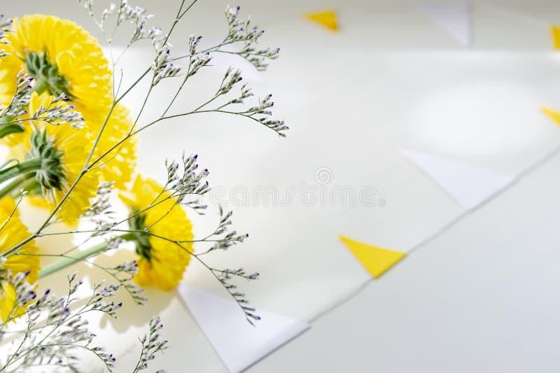 Букет желтых хризантем лежит на белой таблице окруженной гирляндой флагов стоковые изображения rf