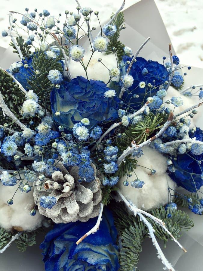 Букет зимы белых и голубых цветков Букет цветков включая голубые розы покрытые со снегом, конусы, ветви ели, шарик хлопка стоковые фото