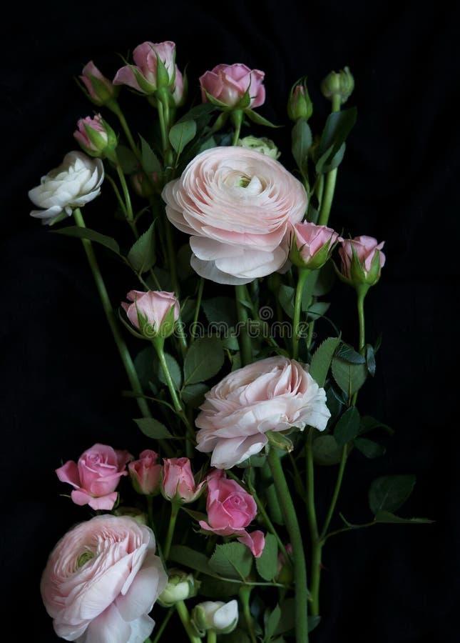 Букет красивого бледнеет - розовые розы и лютик на темной предпосылке стоковое фото