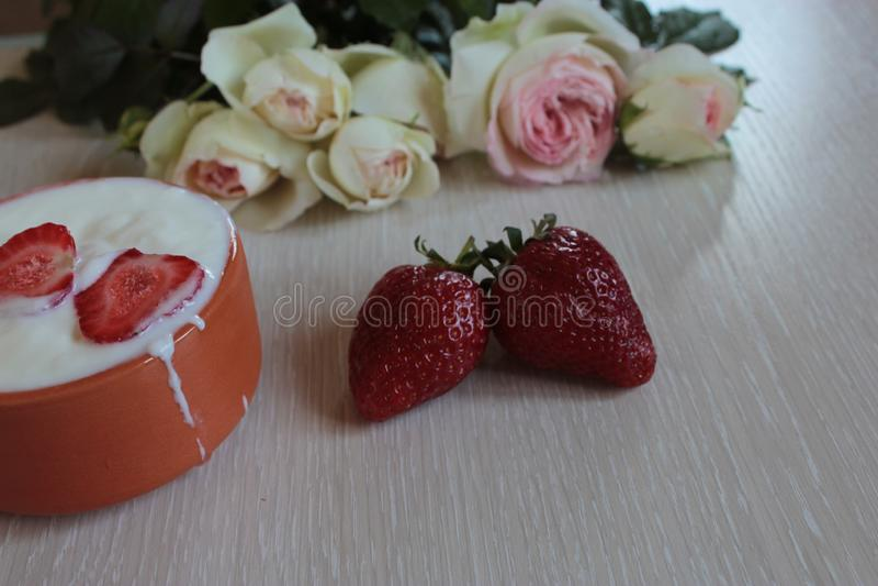 Букет красивой лож красных роз и клубник со сливками на яркой предпосылке стоковые изображения rf