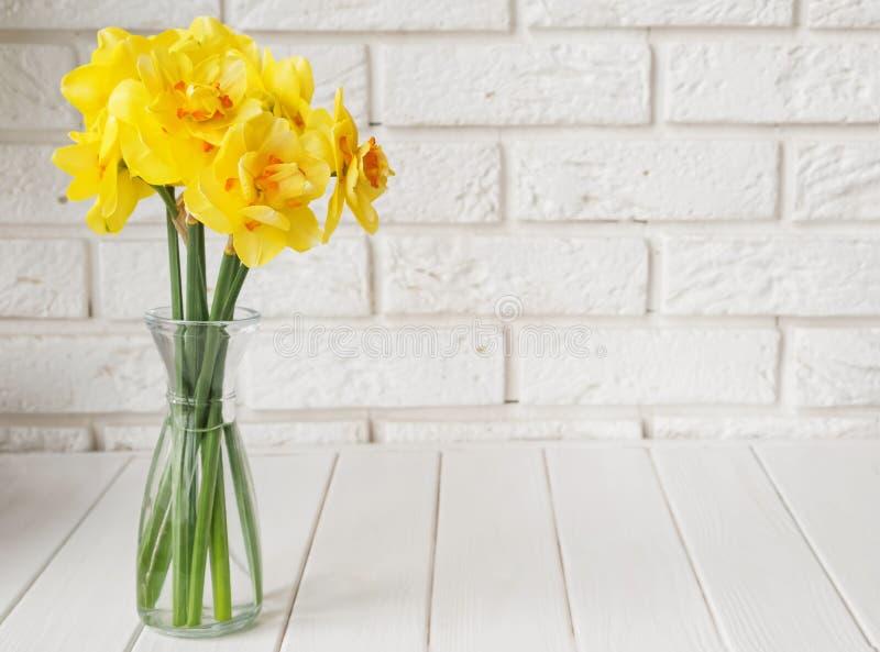 Букет красивых цветков весны над белой кирпичной стеной стоковое изображение