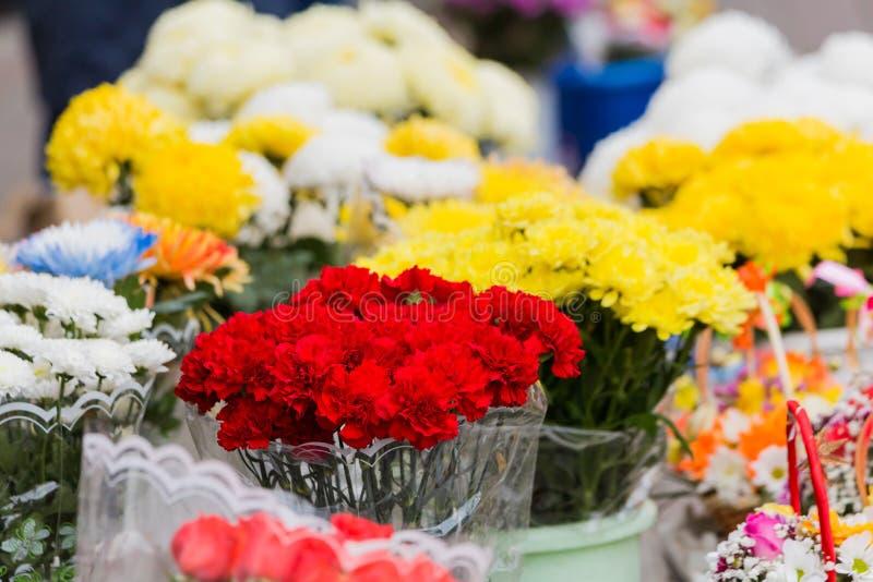 Букет красных гвоздик и другие цветки проданы в рынке города стоковые фотографии rf