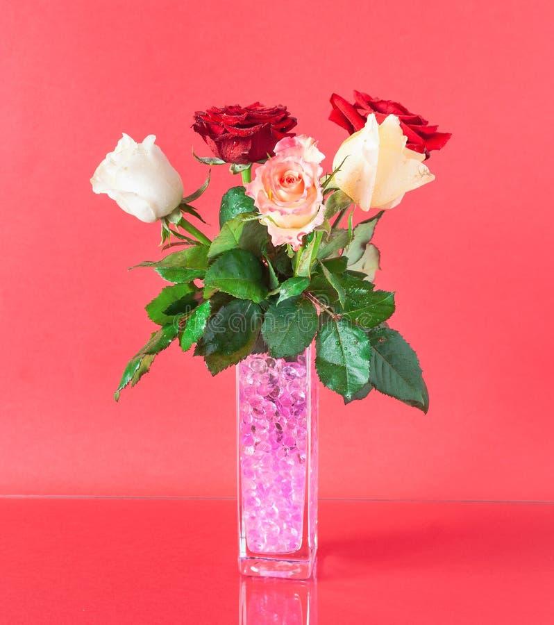Букет красочных роз в декоративной вазе изолированной на красной предпосылке стоковое фото rf