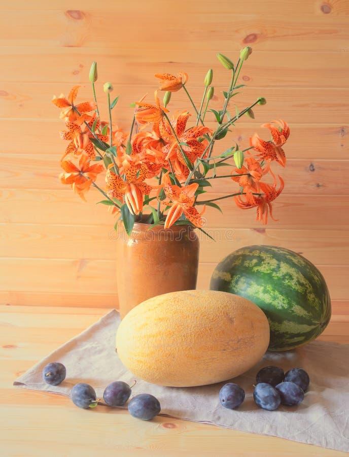 Букет оранжевых лилий, арбуза, дыни и слив близко стоковые фотографии rf