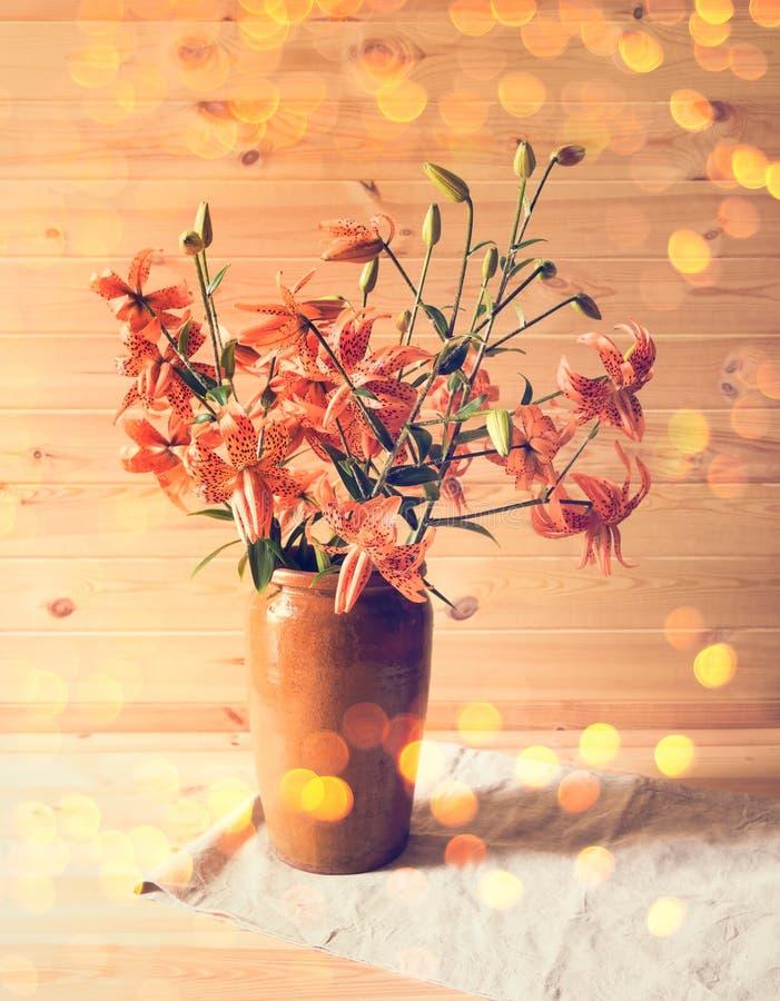 Букет оранжевых лилий в вазе глины тонизированное изображение стоковые фото