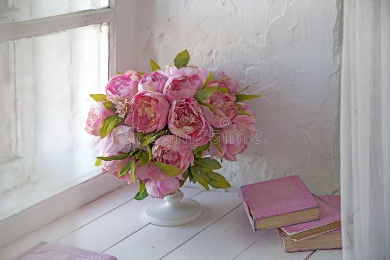 Букет орхидей, пионов, роз в керамической вазе и стога книг стоковые изображения