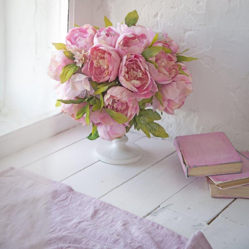 Букет орхидей, пионов, роз в керамической вазе и стога книг стоковые изображения rf