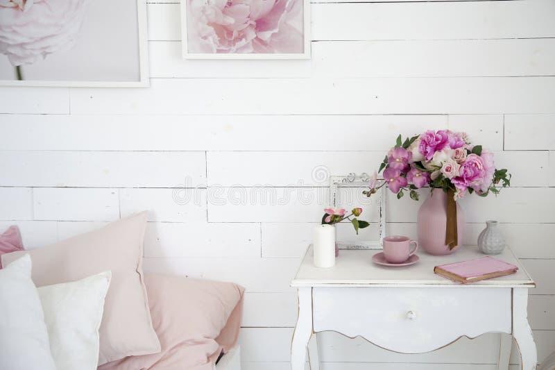 Букет орхидей, пионов, роз в керамической вазе на прикроватном столике и стога книг стоковая фотография