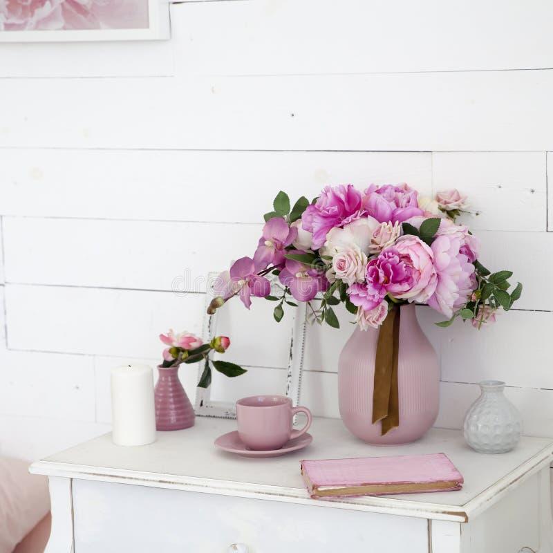 Букет орхидей, пионов, роз в керамической вазе на прикроватном столике и стога книг стоковые фотографии rf
