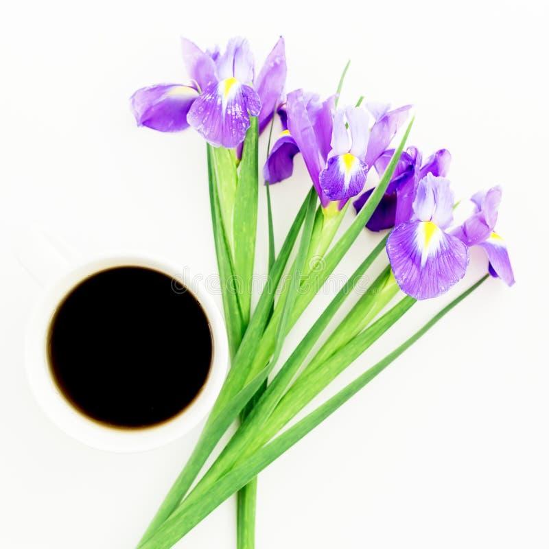 Букет радужки цветет с кружкой черного кофе на белой предпосылке Плоское положение, взгляд сверху стоковые фото