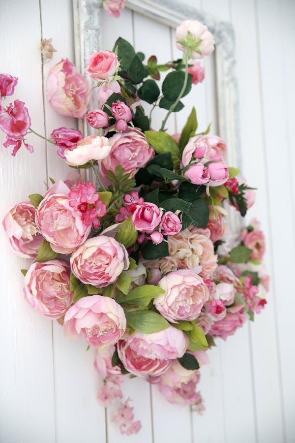 Букет розовых орхидей, роз и пехотинцев в большой рамке вися на стене стоковое изображение