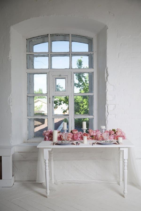 Букет розовых орхидей, роз и пехотинцев украшает обеденный стол около окна стоковое фото