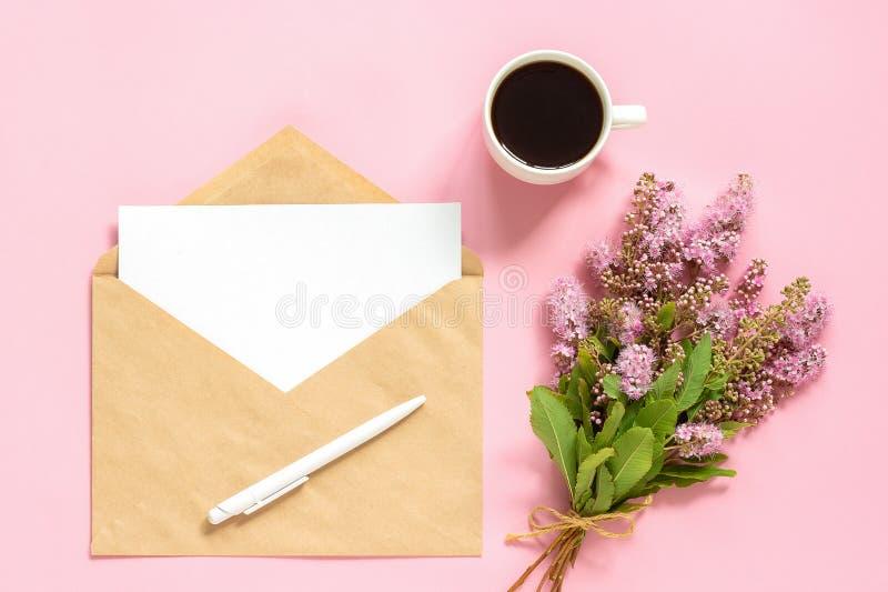 Букет розовых цветков, конверт с белой пустой картой для текста и чашка кофе на розовой насмешке положения поздравительной открыт стоковая фотография rf