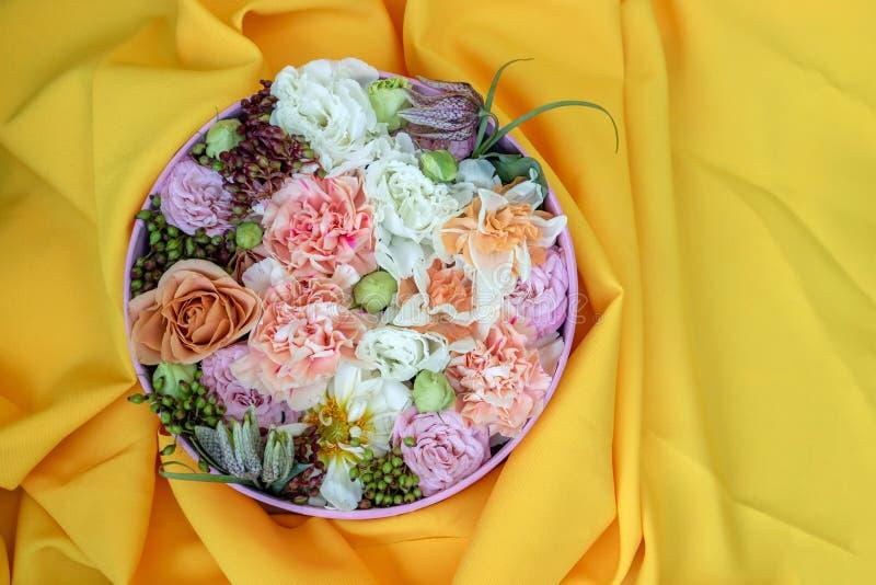 Букет роз, daffodils, eustoma и других цветков на желтой предпосылке Идея цветочной композиции в круглой коробке стоковые изображения rf