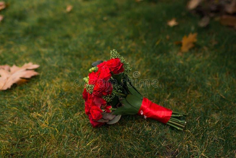 Букет свадьбы при розы красных роз лежа на зеленой траве стоковая фотография rf