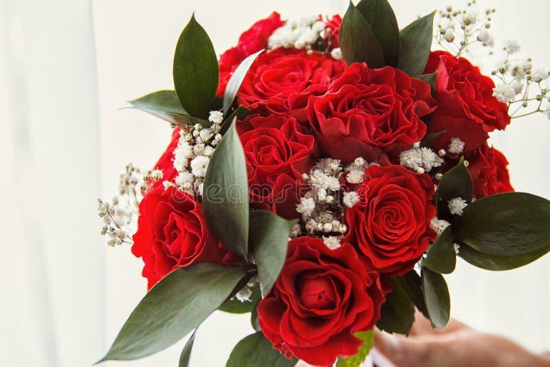 Букет свадьбы сделанный из красных роз и цветков гвоздики на белой деревянной поверхности стоковое фото rf