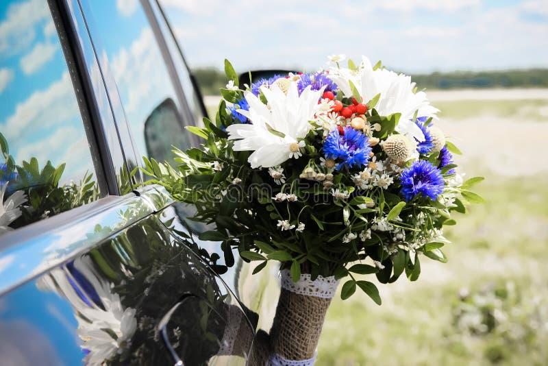 Букет свадьбы на двери черного автомобиля стоковое изображение