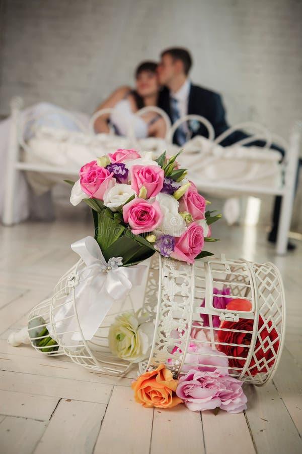 Букет свадьбы от роз и счастливой невесты и жизнерадостный groom лежат на кровати в спальне стоковые фото