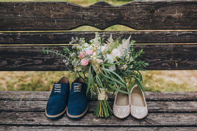 Букет свадьбы цветков и растительности и жениха и невеста ботинок лежа на старой деревянной скамье стоковые изображения