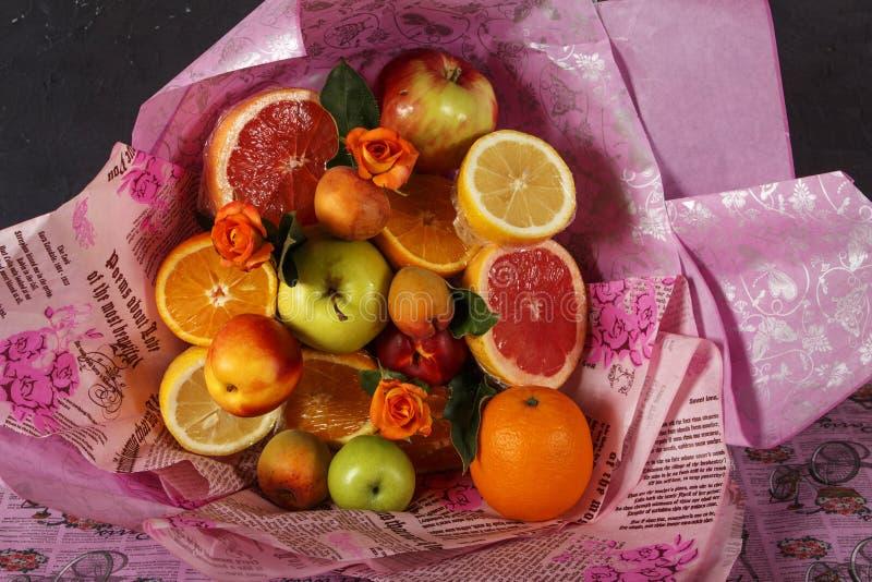 Букет свежих фруктов при цитрус и розы обернутые в красочной упаковочной бумаге Букет плодоовощ с свежими фруктами и цветками стоковое фото rf
