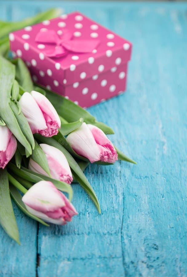 Букет тюльпанов и подарочной коробки на backgr бирюзы деревенском деревянном стоковые фотографии rf