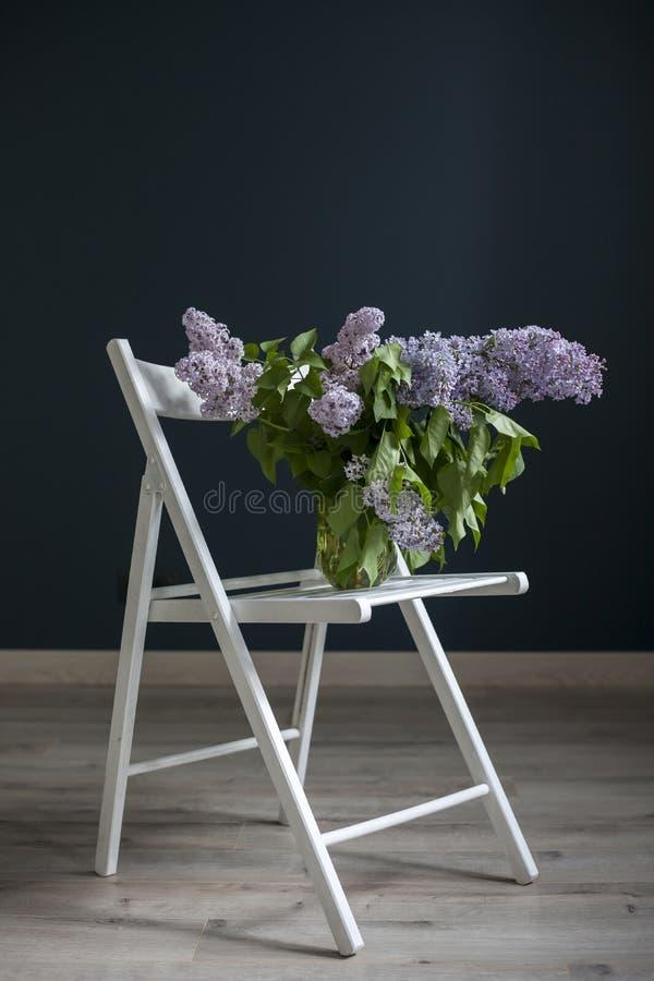 Букет хворостин сирени в прозрачном зеленом опарнике на белом стуле как украшение внутренней противоположности черной стены стоковые изображения rf