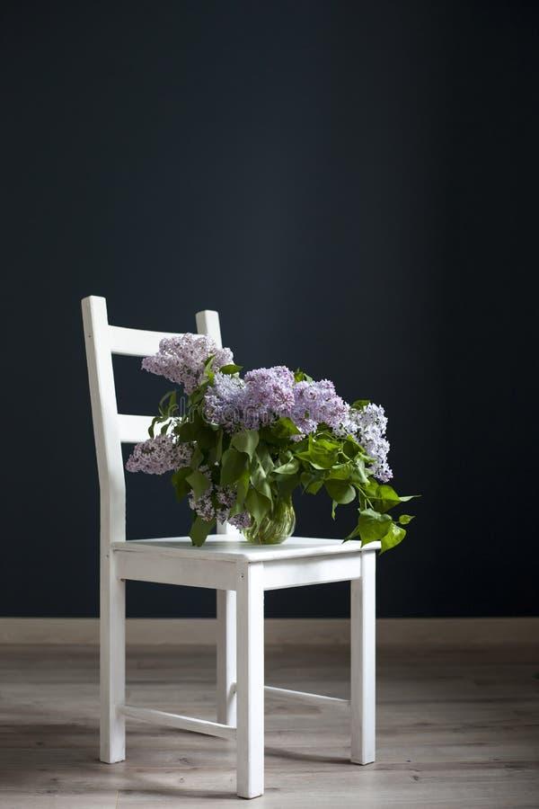 Букет хворостин сирени в прозрачном зеленом опарнике на белом стуле как украшение внутренней противоположности черной стены стоковая фотография rf