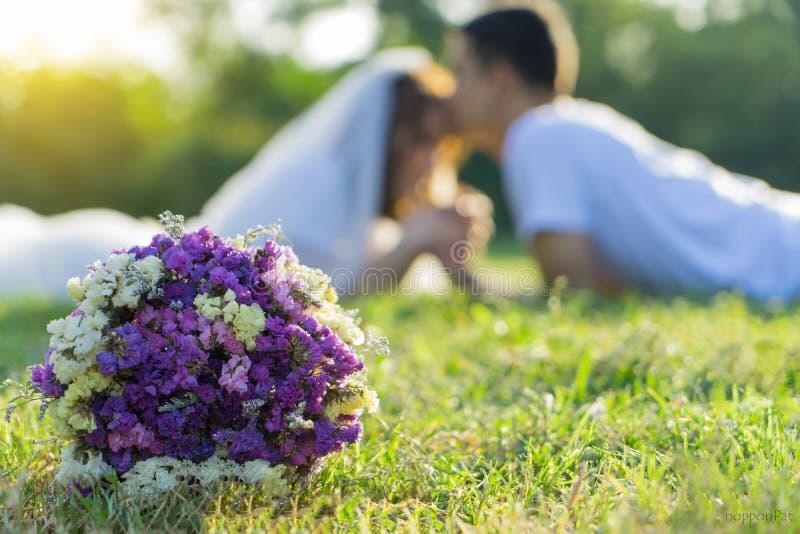 Букет цветка с запачканным женихом и невеста мягкого фокуса счастливым совместно после свадебной церемонии, на открытом воздухе к стоковые изображения rf