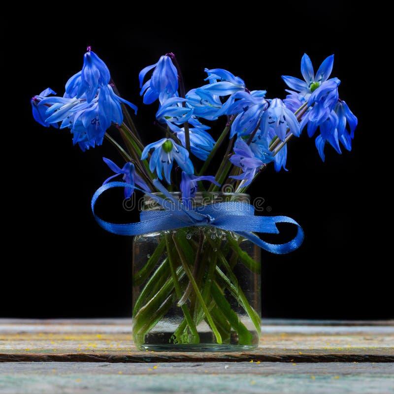 Букет цветка bluebell в вазе на таблице на черной предпосылке стоковое фото