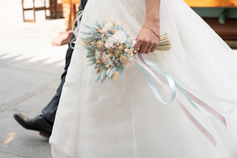 букет цветков свадьбы в руках невесты в белом длинном платье стоковое фото rf