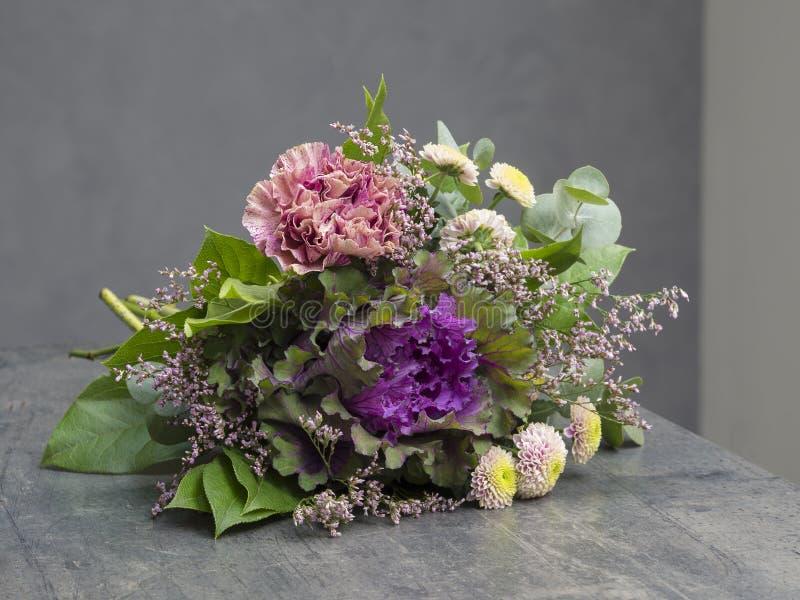 Букет цветков украшает дырочками фиолетовое и зеленую с декоративной капустой стоковые изображения