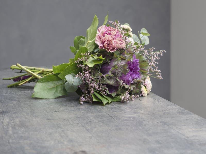 Букет цветков украшает дырочками фиолетовое и зеленую с декоративной капустой стоковое фото