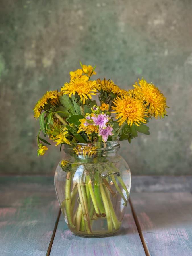 Букет цветя одуванчиков и небольшое hyancite в стеклянном опарнике стоя на деревянном столе стоковые изображения