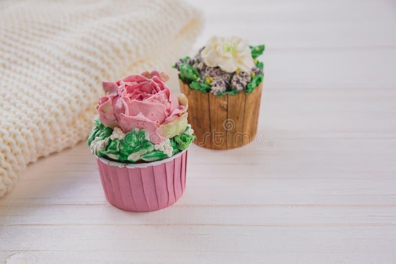 2 булочки с покрашенными цветками масла на белом деревянном столе с яркой предпосылкой зеленых цветов стоковые фото