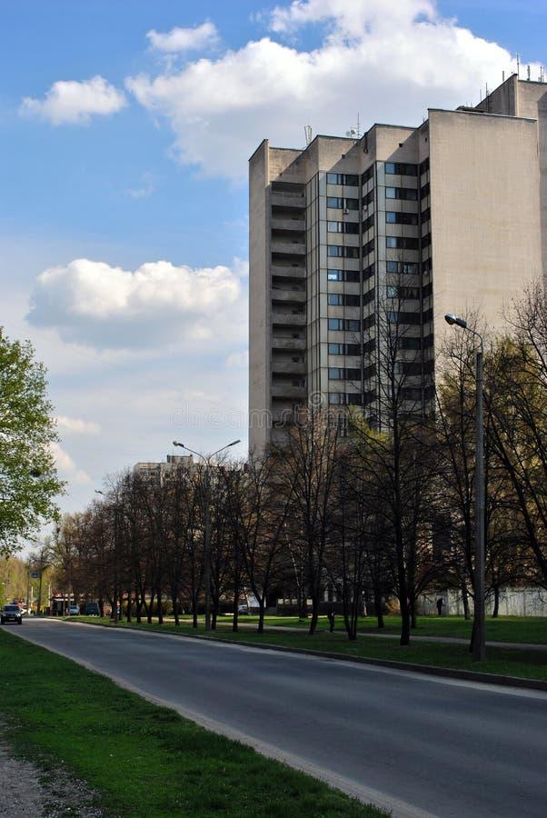 Бульвар деревьев и уличных светов вдоль дороги с высоким офисным зданием этажа в городе, голубом небе стоковые фотографии rf