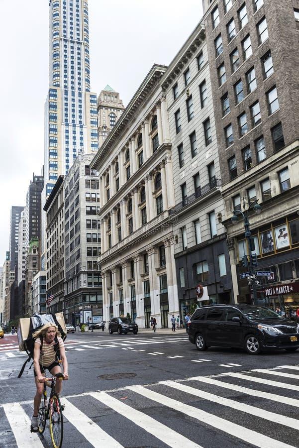 Бульвар Пятого авеню 5-ый с велосипедистом нося связку и людей вокруг и движение внутри стоковые фото