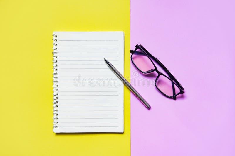 Бумага блокнота или тетради с ручкой и стекла на желтом пинке для образования и концепции дела стоковая фотография