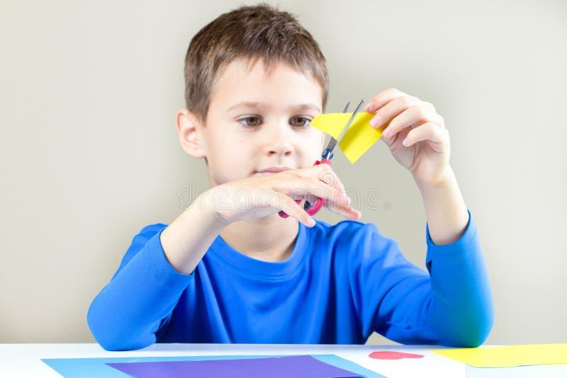 Бумага вырезывания мальчика покрашенная с ножницами на таблице стоковая фотография