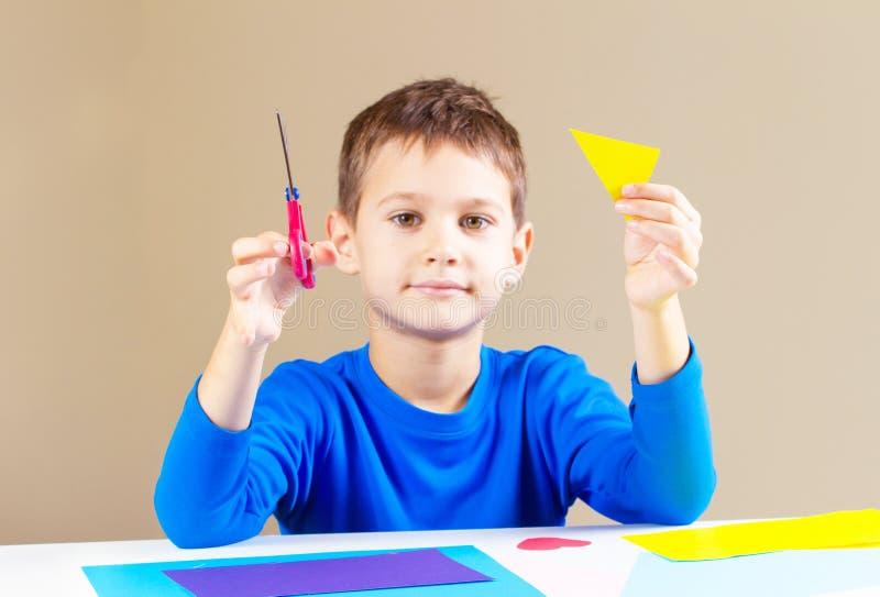 Бумага вырезывания мальчика покрашенная с ножницами на таблице стоковые изображения rf