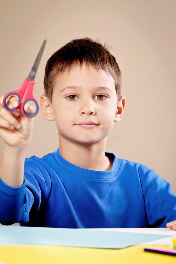 Бумага вырезывания мальчика покрашенная с ножницами на таблице стоковые фотографии rf
